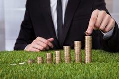 Businessman arranging coins Stock Photo