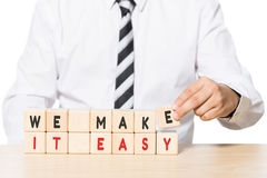 Businessman Arranging Wooden Blocks with we make it easy words Stock Image