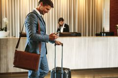 Businessman arriving at hotel lobby. Businessman standing in hotel lobby with suitcase and using his mobile phone. Male business traveler in hotel hallway with Stock Photography