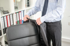 Businessman arriving at office. Businessman placing his jacket over his chair Royalty Free Stock Images