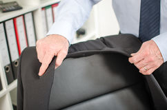 Businessman arriving at office. Businessman placing his jacket over his chair Stock Image