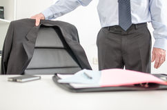 Businessman arriving at office. Businessman about to sit at his desk Stock Image