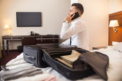 Businessman Arriving to Hotel. Rear view portrait of successful businessman speaking by phone after arriving to hotel while unpacking luggage Royalty Free Stock Image