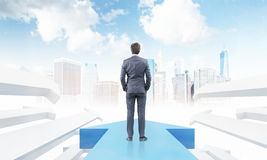 Businessman on arrow. Businessman standing on large blue arrow pointing to city with skyscrapers. White arrows by his sides. Concept of international company. 3d Stock Photos