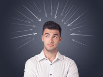 Businessman with arrows. Young casual businessman with arrows pointing to his head Stock Image