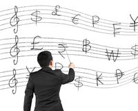 Businessman as a conductor facing money stave Royalty Free Stock Photo