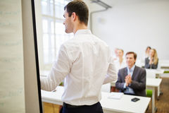 Businessman as a speaker receiving applause from the audience Stock Photo