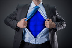 Businessman as super hero and tearing his shirt. Young businessman acting like a super hero and tearing his shirt off Stock Photography