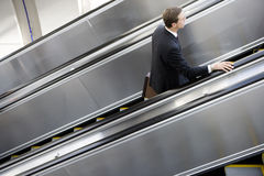 Businessman ascending escalator, side view, elevated view Royalty Free Stock Photo