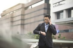 Businessman asian talking on mobile phone and looking watch. Hustle concept Royalty Free Stock Images
