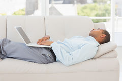 Businessman asleep on the couch with laptop Royalty Free Stock Photography