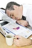 Businessman asleep at his desk on white background Stock Image