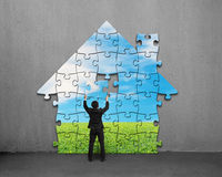 Businessman assembling house shape puzzles with beautiful landsc. Ape on concrete wall Stock Images