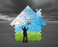 Businessman assembling house shape puzzles with nature image. Against cloudy sky royalty free illustration