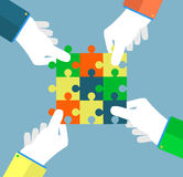 Businessman assembling jigsaw puzzle Stock Image
