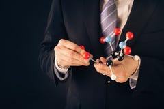 Businessman assembling a tnt molecular structure Royalty Free Stock Photos