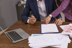 Businessman and assistant working with documents at table stock photography