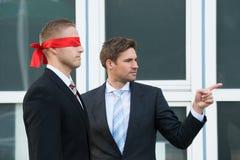 Businessman Assisting Blindfolded Partner Royalty Free Stock Photos