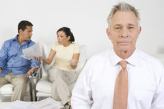 Businessman Assisting Couple. Senior financial advisor with couple arguing in background Royalty Free Stock Image