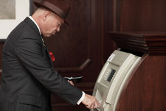 Businessman at an atm machine Royalty Free Stock Photos