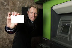 Businessman and an atm machine Stock Photography