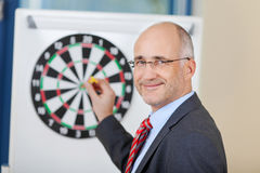 Businessman Attaching Dart On Target In Office Royalty Free Stock Photos