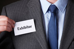 Businessman Attaching Exhibitor Badge To Jacket. Businessman Attaches Exhibitor Badge To Jacket Stock Photo