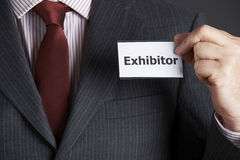Businessman Attaching Exhibitor Badge To Jacket. Close Up Of Businessman Attaching Exhibitor Badge To Jacket Stock Photo