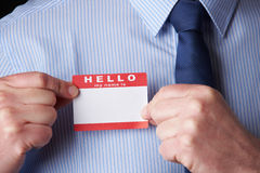 Businessman Attaching Name Tag At Conference. Businessman Attaches Name Tag At Conference Stock Photo