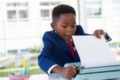 Businessman attaching paper in typewriter Stock Photos