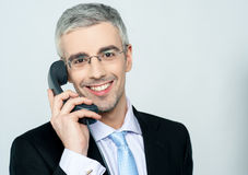 Businessman attending phone call. Smiling aged businessman speaking with client Stock Photos