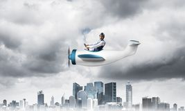 Businessman in aviator hat driving paper plane stock images