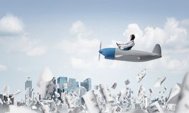 Businessman driving propeller plane above downtown stock photography