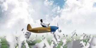 Businessman in aviator hat driving plane stock image