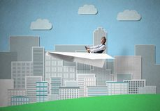 Businessman in aviator hat sitting in paper plane stock image