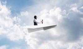 Businessman in aviator hat sitting in paper plane stock photos