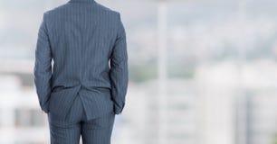 Businessman back against windows Stock Photography