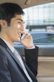 Businessman in Back Seat of Car on the Phone Stock Images