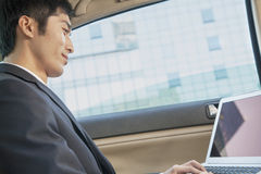 Businessman in Back Seat of Car Typing on Laptop, Low Angle View Stock Images