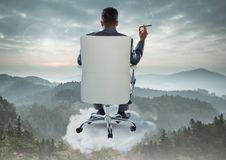 Businessman Back Sitting in Chair with cigar on cloud over mountain landscape Stock Images