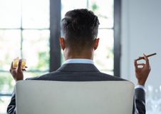 Businessman Back Sitting in Chair with cigar and drinks glass by window Royalty Free Stock Images