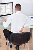 Businessman with backache using computer at desk Stock Images