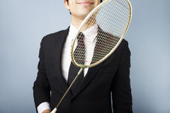 Businessman with badminton racket. Smiling young multiracial businessman holding badminton racket Royalty Free Stock Photo