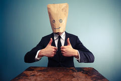 Businessman with bag over head giving thumbs up Royalty Free Stock Image