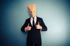 Businessman with bag over head giving two thumbs up Stock Images