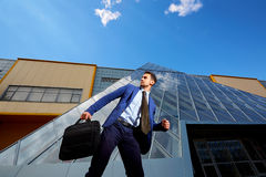 Businessman with bag running and looking back. Royalty Free Stock Images