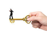 Businessman balance on treasure key in dollar sign shape Royalty Free Stock Images