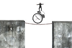 Businessman balancing alarm clock on rusty chain connected concr Royalty Free Stock Photos