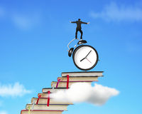 Businessman balancing on alarm clock and stack of books Stock Image