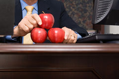 Businessman balancing apples on desk Stock Photo